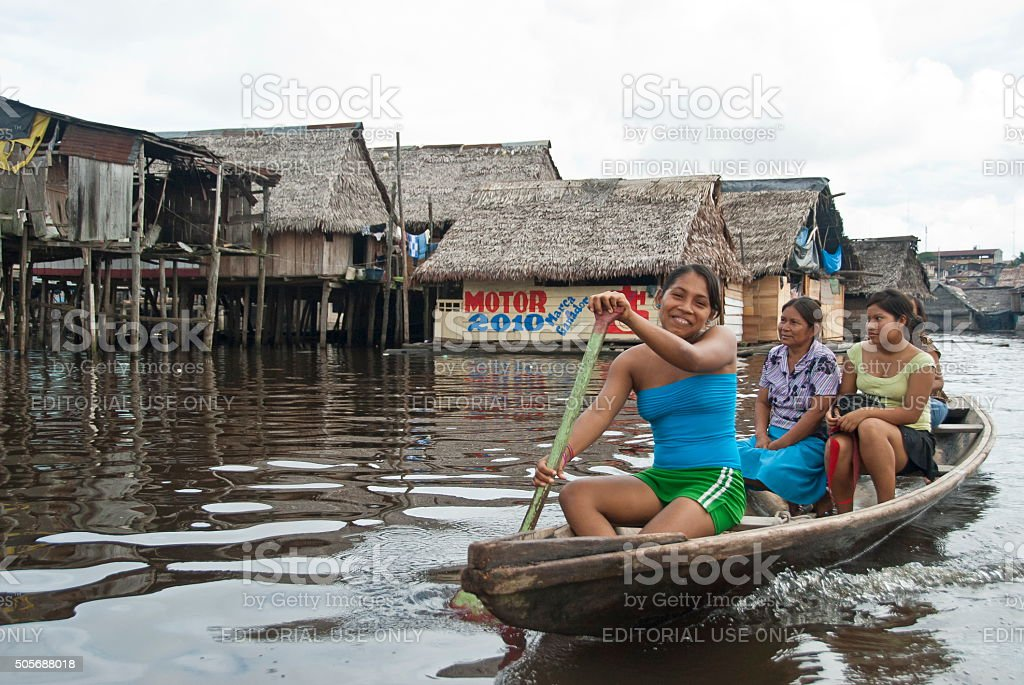 Peruvian family floats on water street in Belen, Iquitos, Peru. stock photo