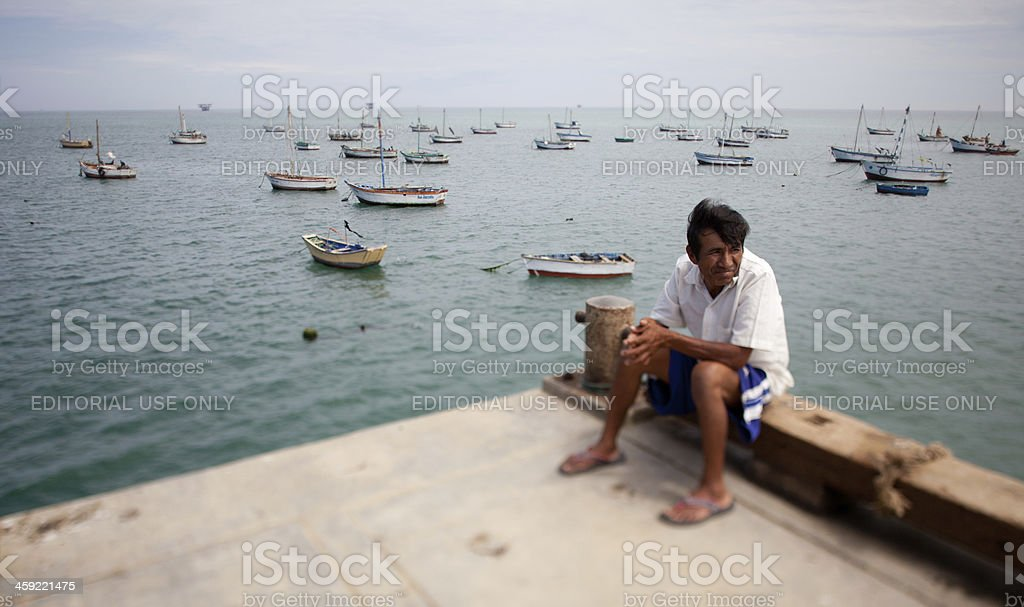 Peruvian Fisherman sitting on the Pier stock photo
