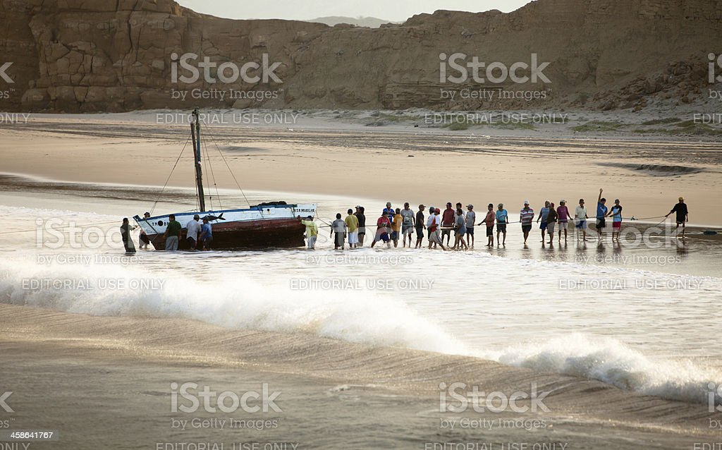 Peruvian fishermen working together to clean their boats royalty-free stock photo