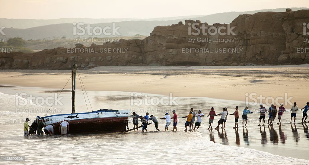 Peruvian fishermen working together to haul boat in for cleaning royalty-free stock photo