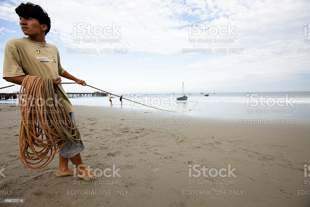 Peruvian fishermen working together to haul their boats in royalty-free stock photo