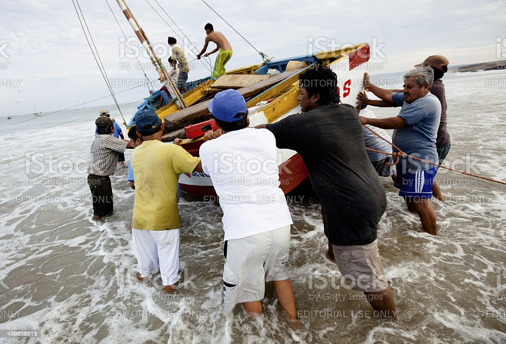 Peruvian fishermen working together to launch a fishing boat royalty-free stock photo
