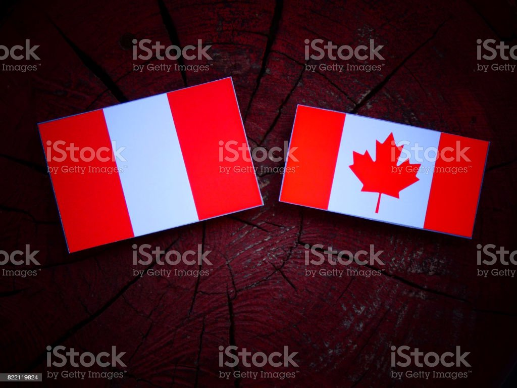 Peruvian flag with Canadian flag on a tree stump isolated stock photo
