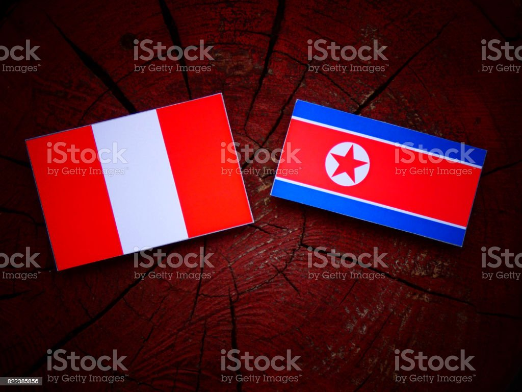 Peruvian flag with North Korean flag on a tree stump isolated stock photo