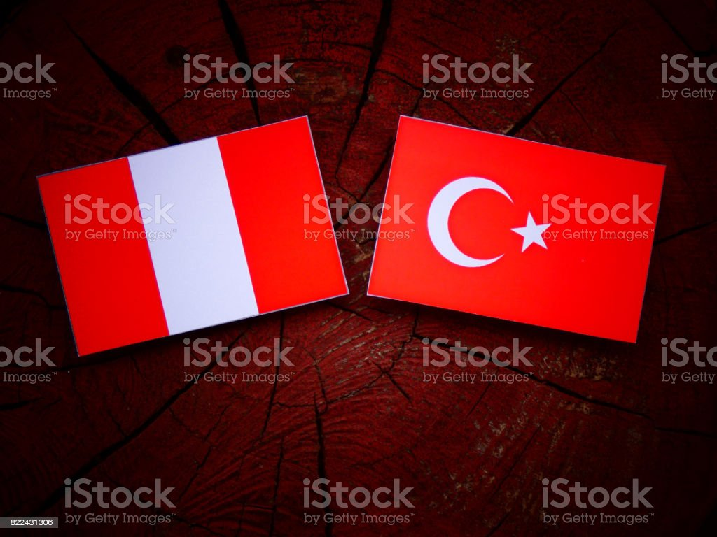 Peruvian flag with Turkish flag on a tree stump isolated stock photo