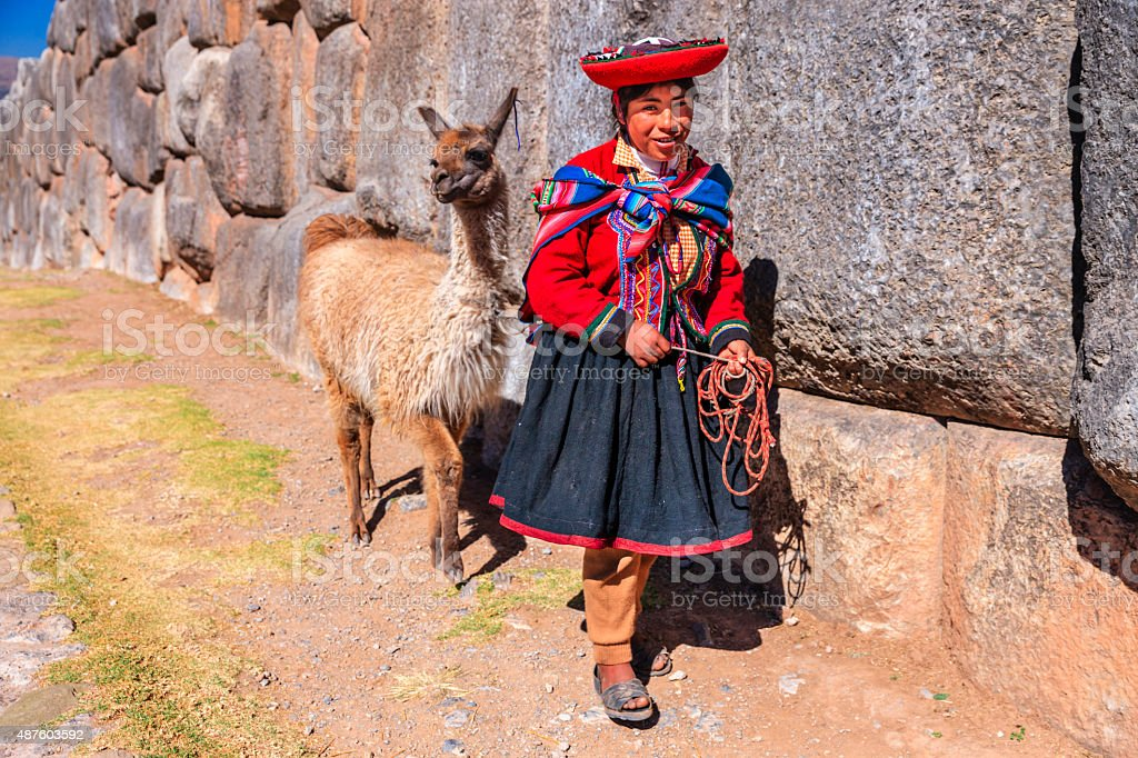 Peruvian girl wearing national clothing posing with llama near Cuzco stock photo