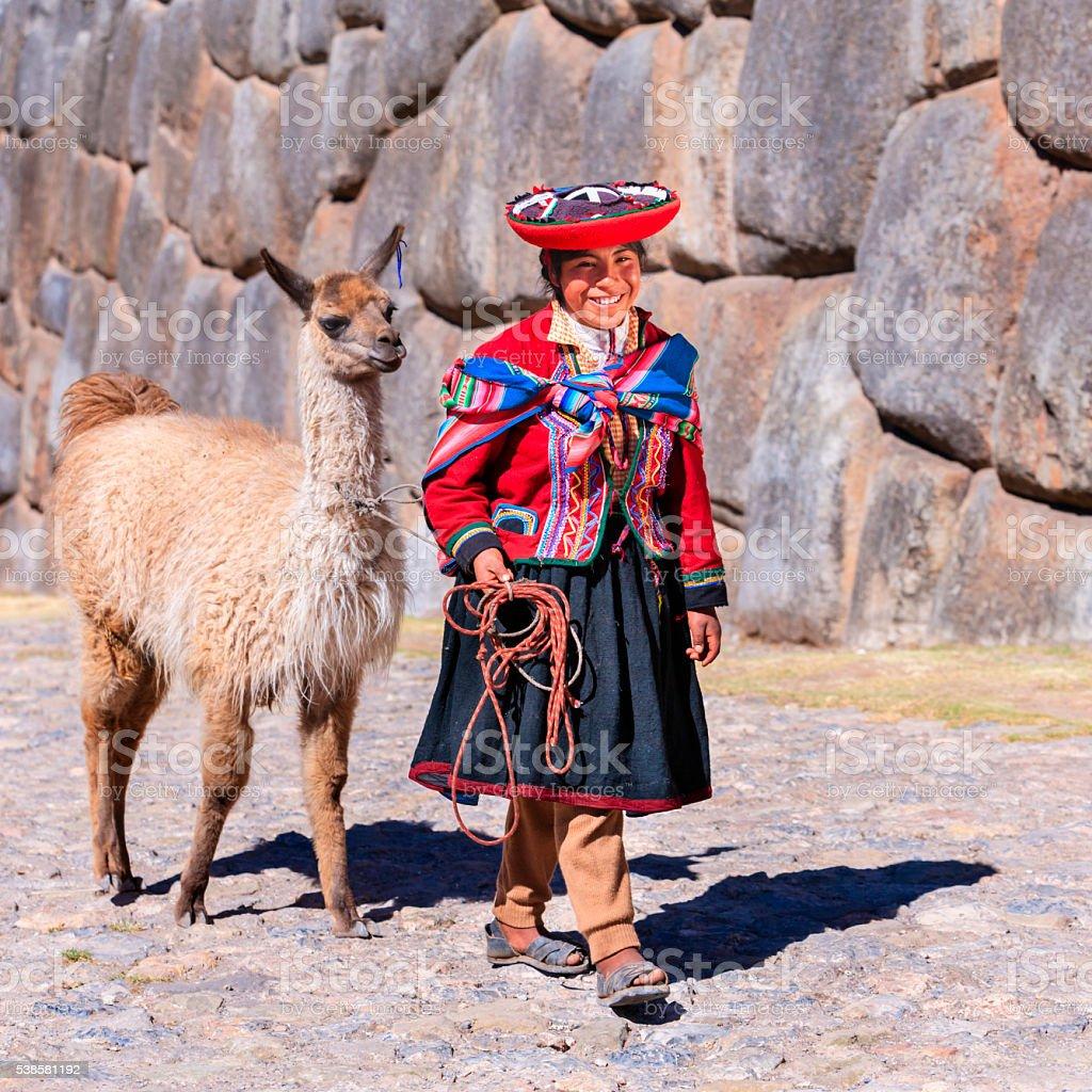 Peruvian girl wearing national clothing walking with llama near Cuzco stock photo