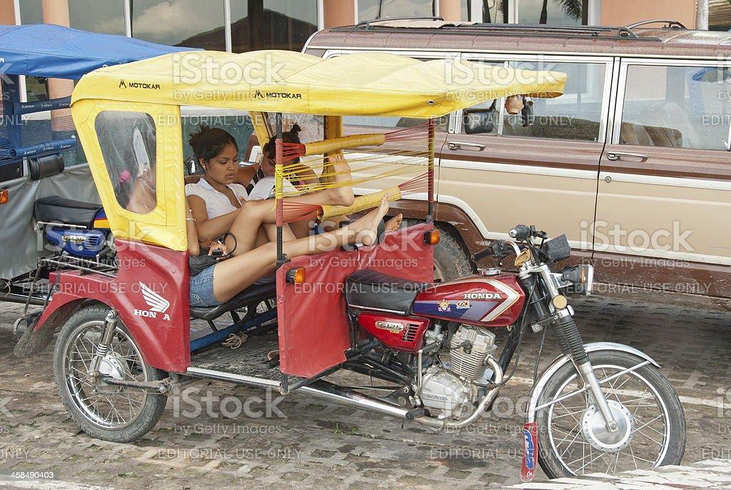 Peruvian girls wait in a motocarro their driver. stock photo