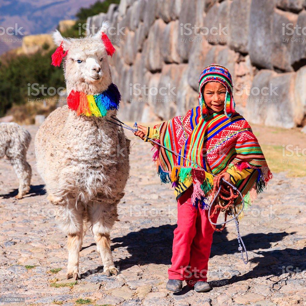 Peruvian little boy wearing national clothing with llama near Cuzco stock photo