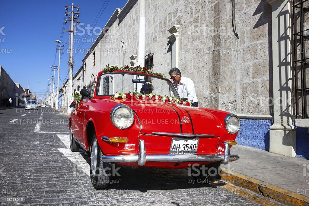 Peruvian man preparing vintage car for wedding royalty-free stock photo