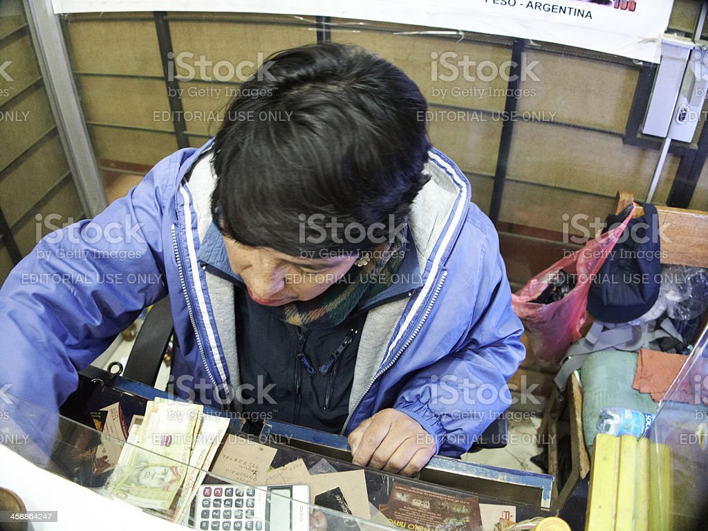 Peruvian woman currency exchange booth stock photo