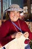 Peruvian woman in national clothing knitting in workshop, Chivay, Peru