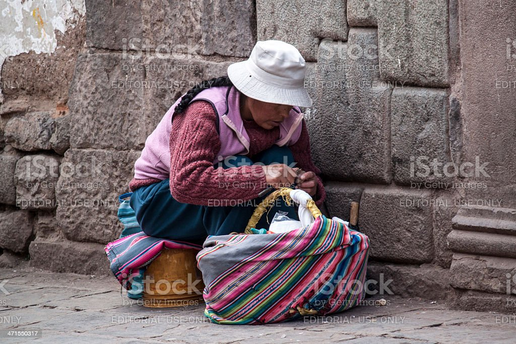Peruvian woman peeling potatoes and preparing street food royalty-free stock photo