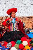 Peruvian woman selling souvenirs at Inca ruins, Sacred Valley, Peru