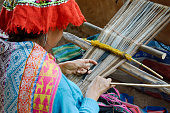 Peruvian woman weaving cloth on a hand loom