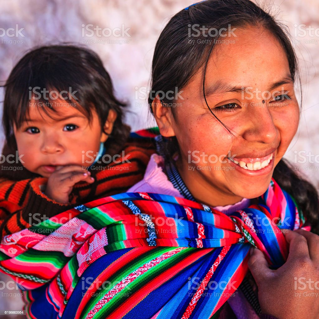 Peruvian woman with her baby on the back near Cuzco stock photo