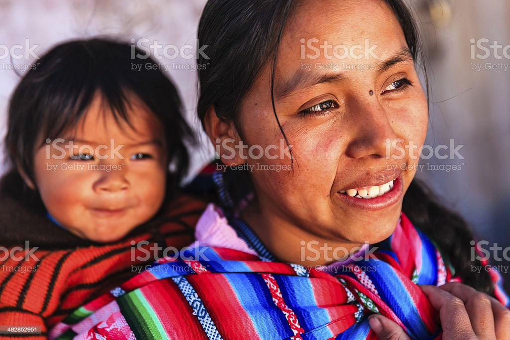 Peruvian woman with her baby on the back, Pisac stock photo