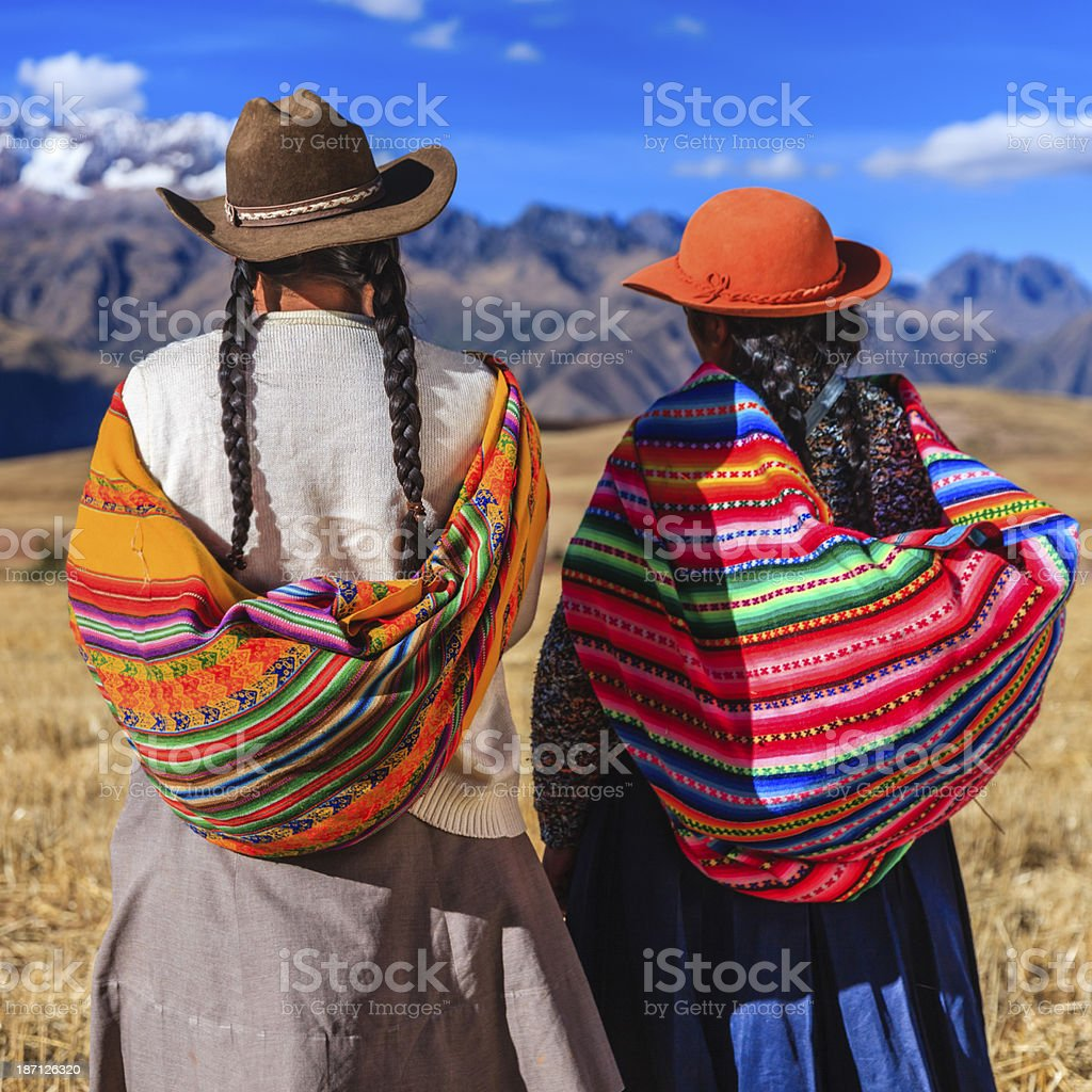 Peruvian women in national clothing crossing field, The Sacred Valley royalty-free stock photo
