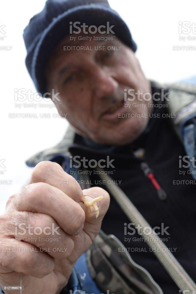 Pescatore con vermi e canna da pesca stock photo
