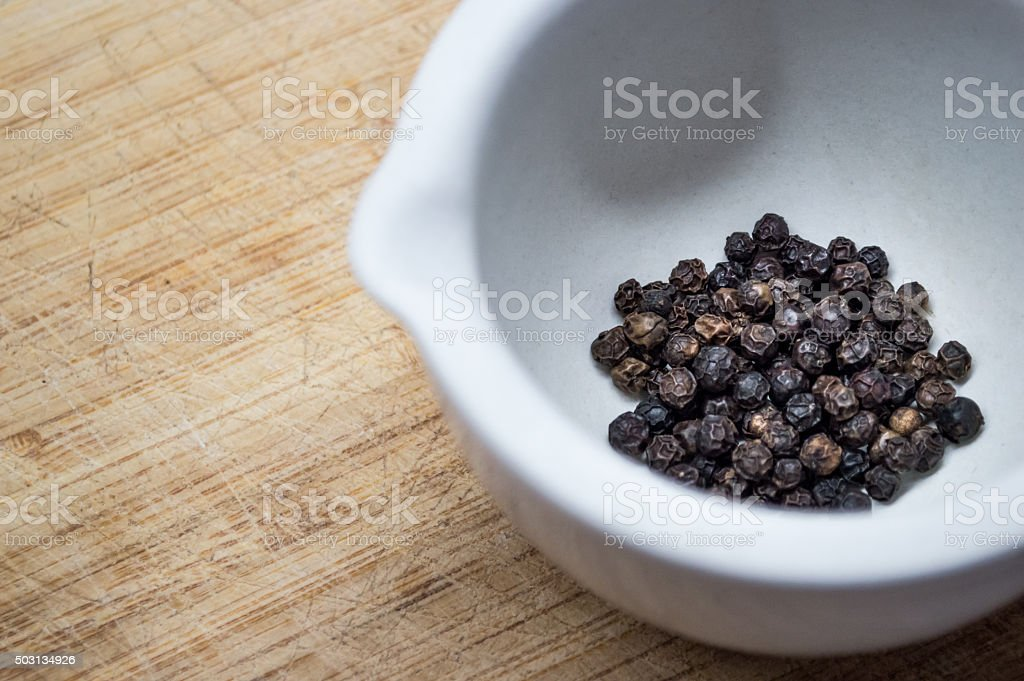 Pestle and Mortar with Black Peppercorn Close Up royalty-free stock photo