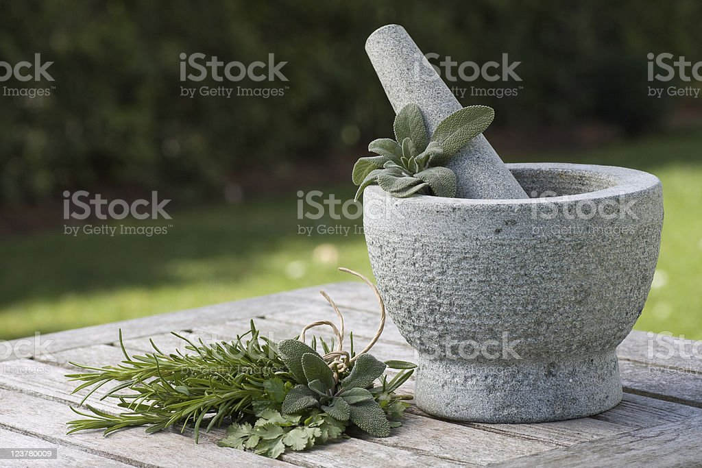 Pestle and mortar with herbs outdoor stock photo