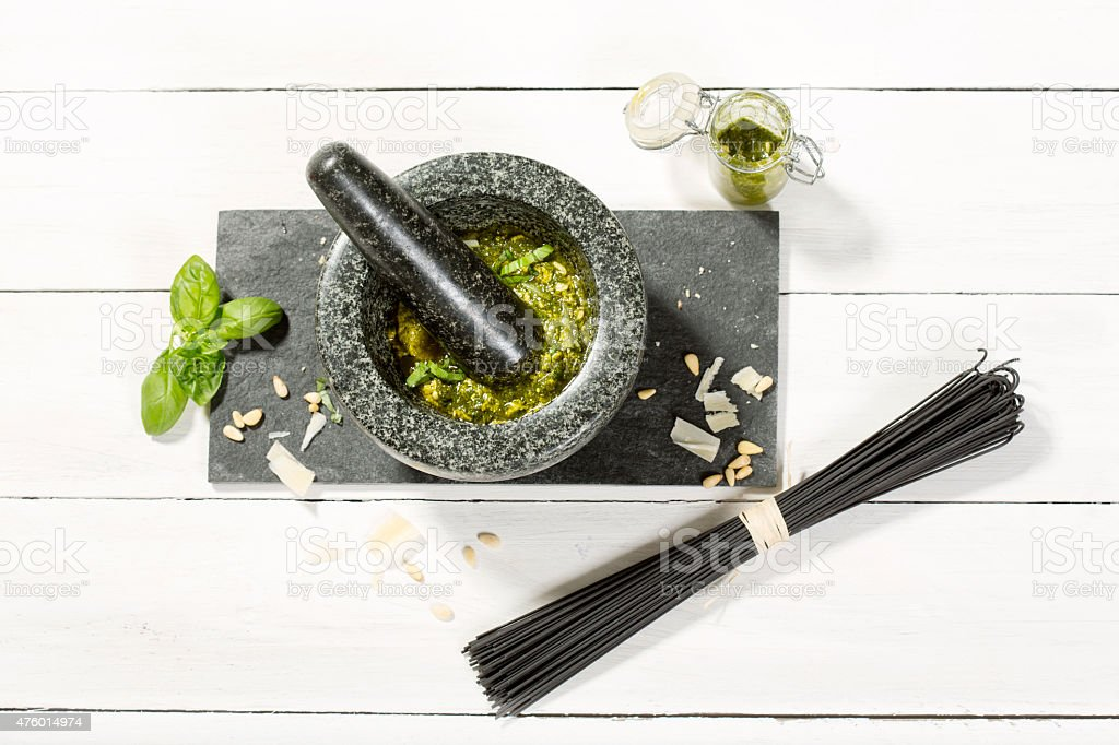 Pesto Genovese in mortar with ingredients and black spaghetti stock photo