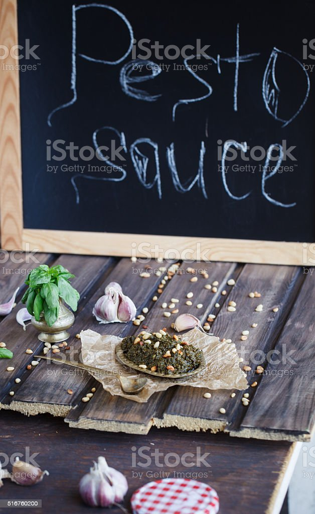 Pesto sauce and ingredients on wooden background stock photo