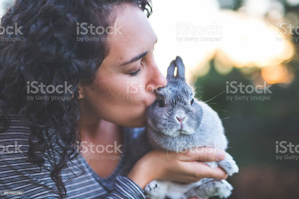 A pet owner is kissing her pet rabbit outdoors during summer