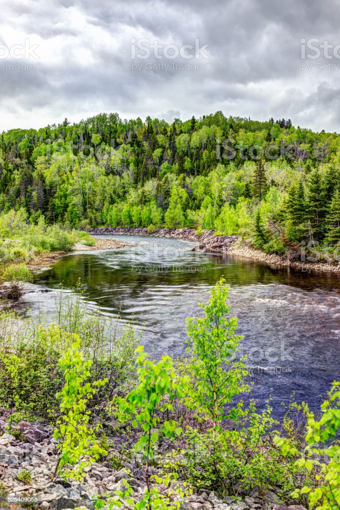 Petit Saguenay river in Quebec, Canada during bright green summer with curve and vertical view stock photo