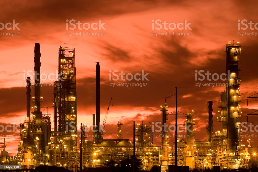 Petrochemical refinery with lights in front of a red sky royalty-free stock photo