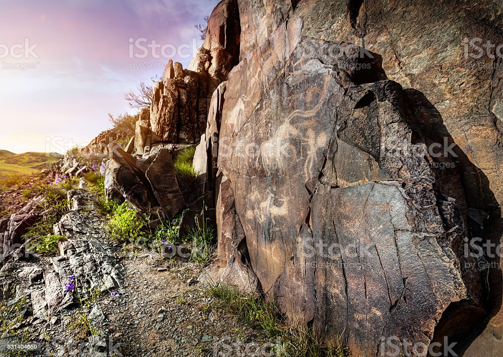 Petroglyph with animals at sunset stock photo