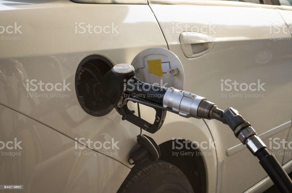 petrol pump nozzle hold by hand with gasoline stock photo