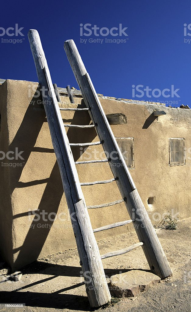 Peublo ladder leaning against an adobe wall stock photo