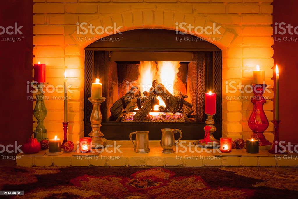 Pewter mugs on candle filled burning fireplace (P) stock photo