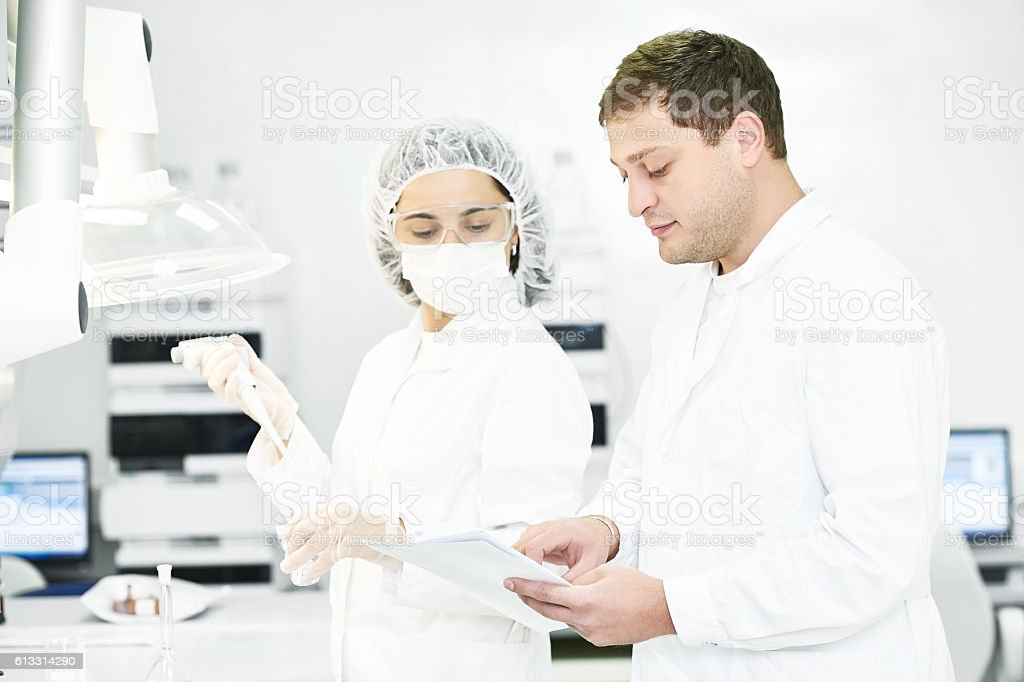 Pharmaceutical staff workers in uniform at laboratory stock photo