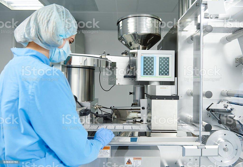 Pharmaceutics. Pharmaceutical worker operates blister packaging machine stock photo