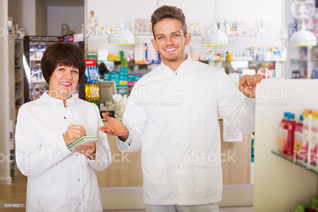 Pharmaceutist working in chemist shop stock photo