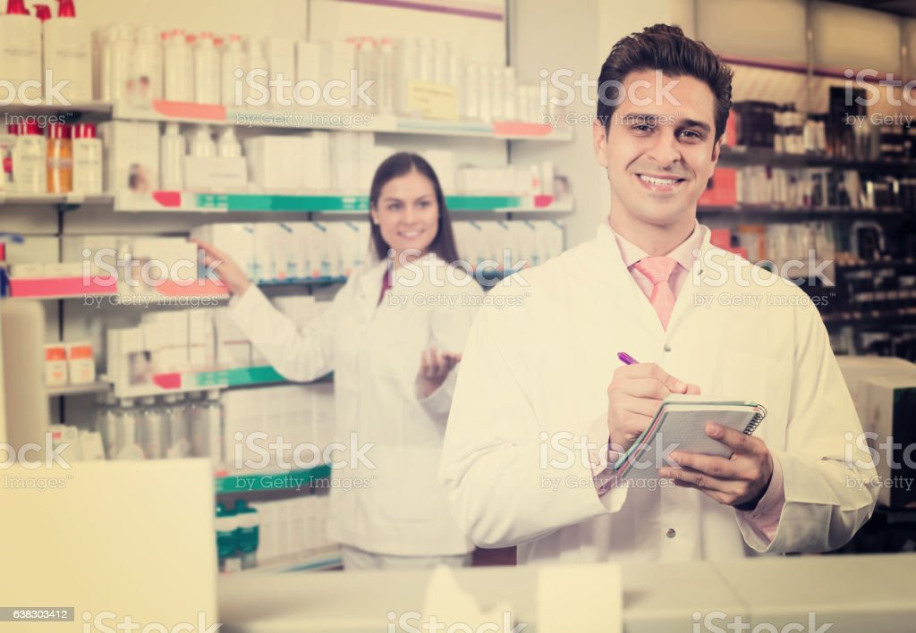 pharmaceutists at reception of drugstore ready to help stock photo