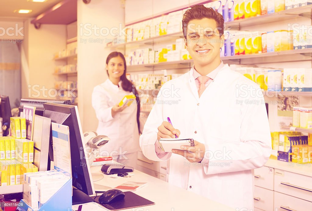 Pharmacist and assistant working stock photo
