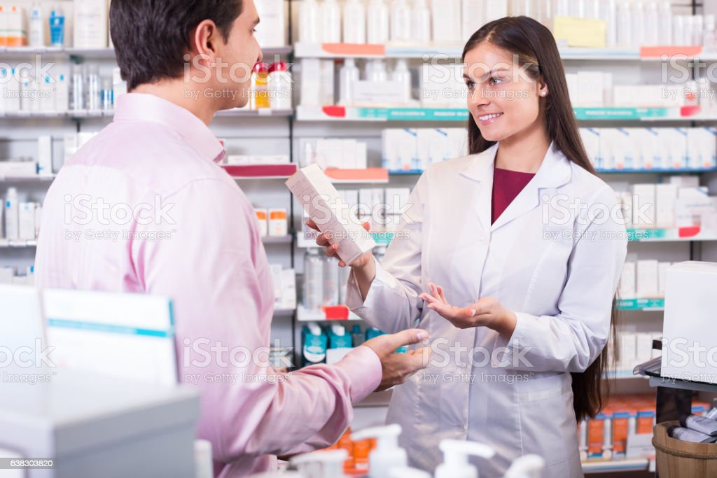 Pharmacist and consulting man in pharmacy stock photo