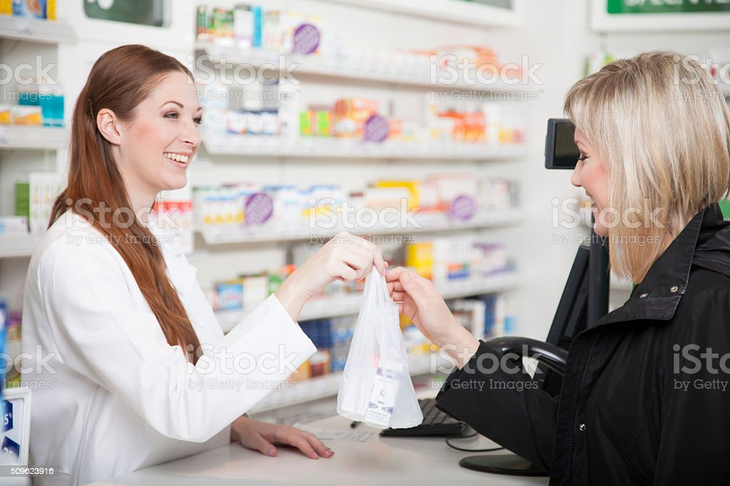Pharmacist and customer in pharmacy stock photo