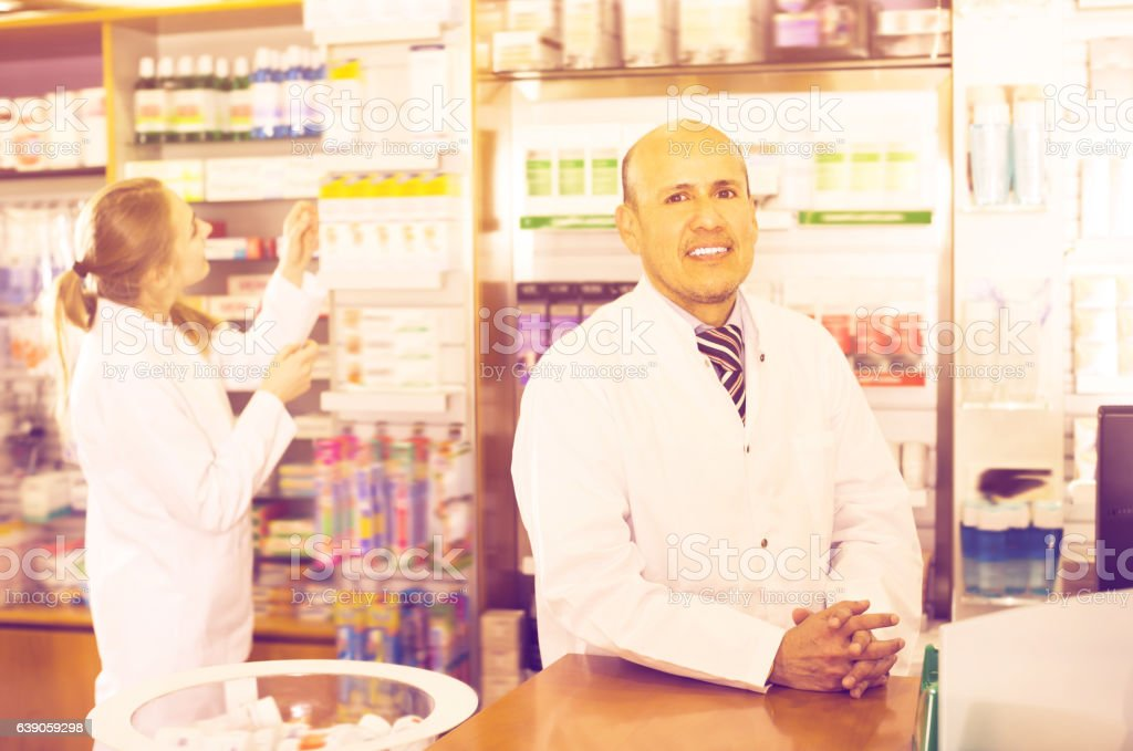 Pharmacist and female assistant helping stock photo