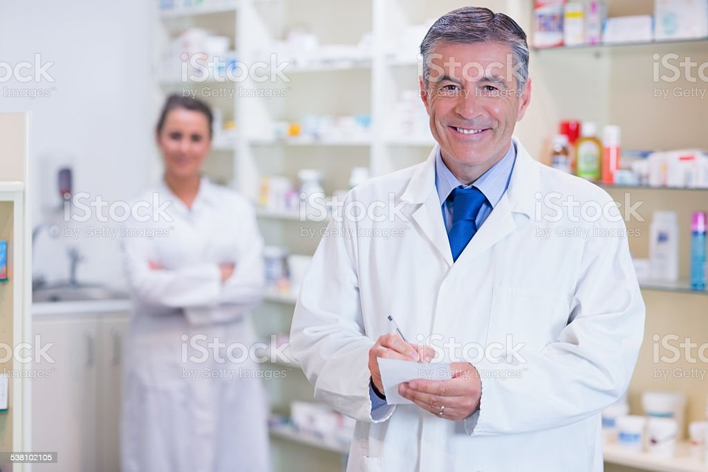 Pharmacist and his trainee with arms crossed behind stock photo