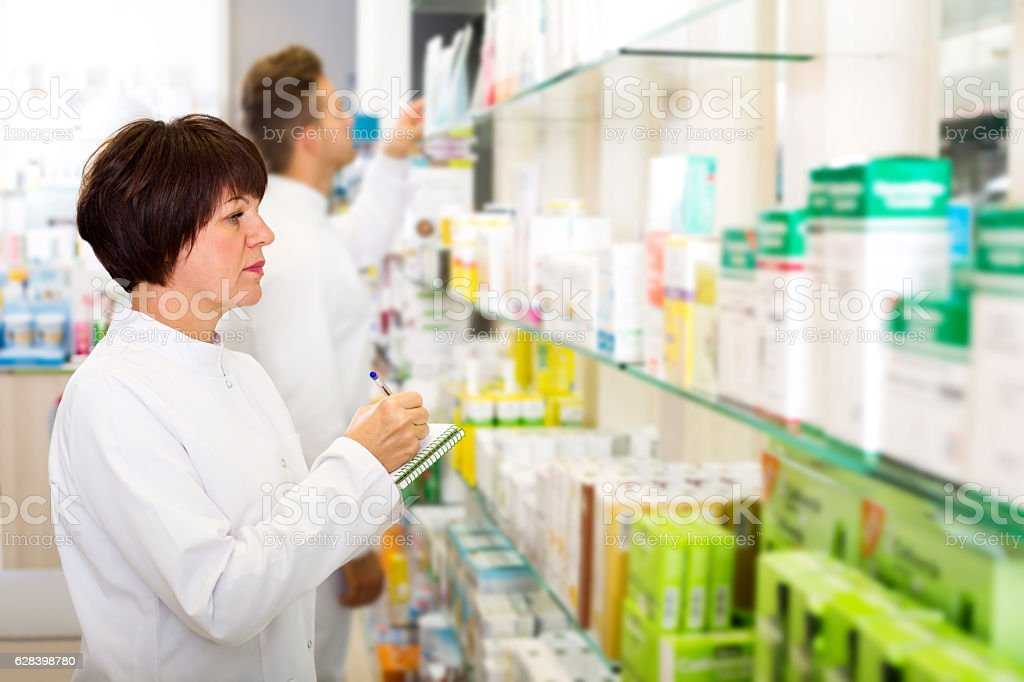 Pharmacist and pharmacy technician posing in drugstore stock photo
