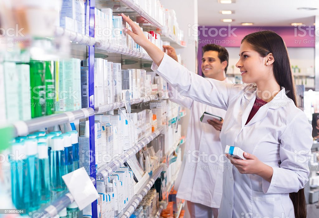 Pharmacist and pharmacy technician posing stock photo