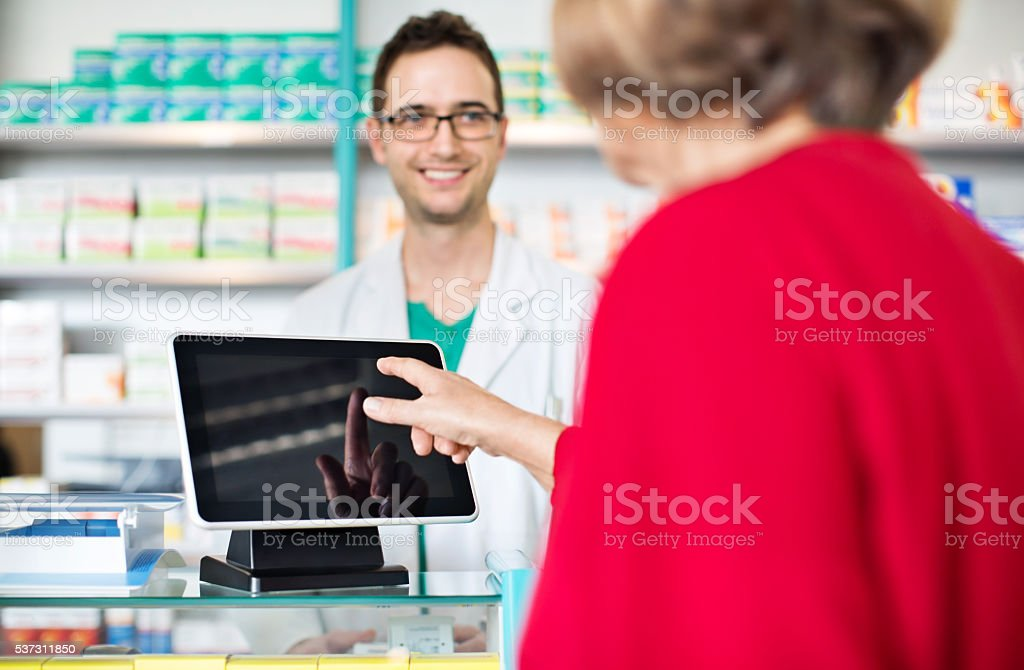 Pharmacist at checkout counter with customer paying through digital tablet stock photo