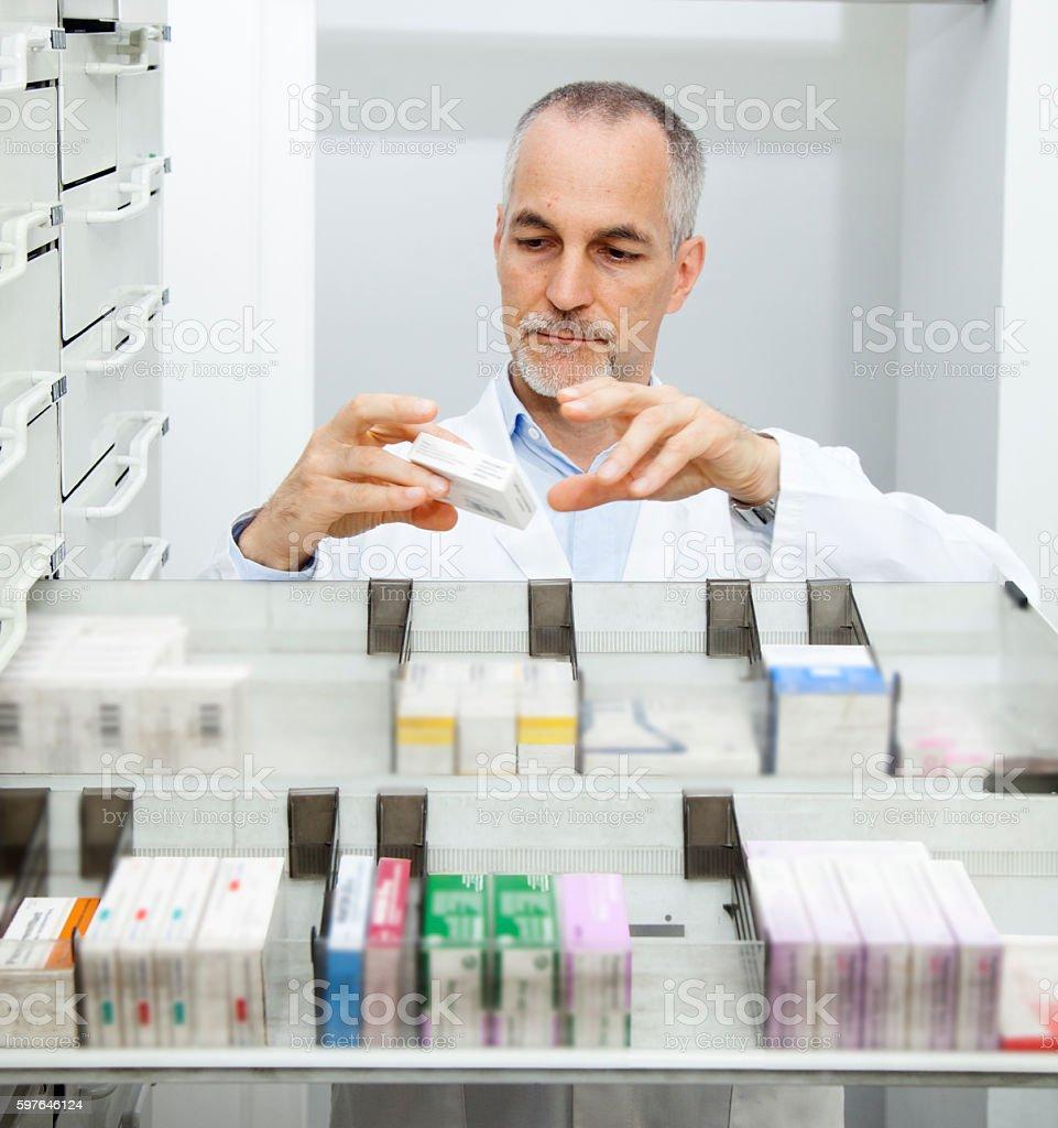 Pharmacist at his pharmacy ordering drugs stock photo