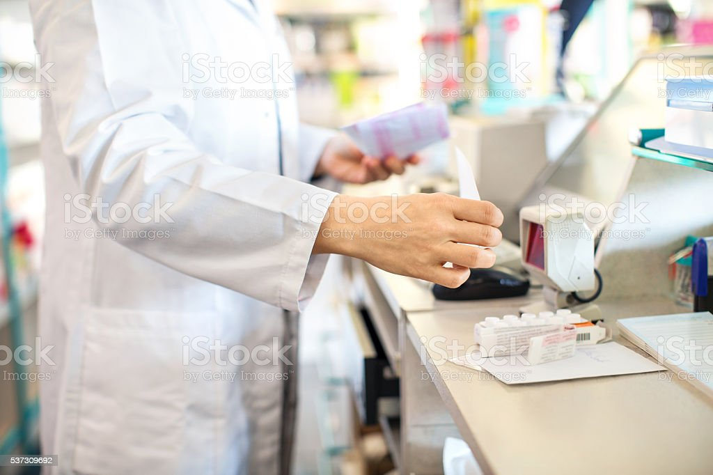 Pharmacist checking out customer's medication prescription stock photo