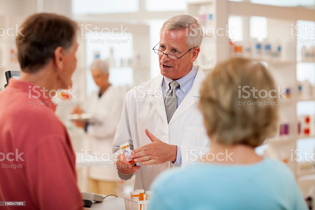 Pharmacist Consulting with Customers stock photo