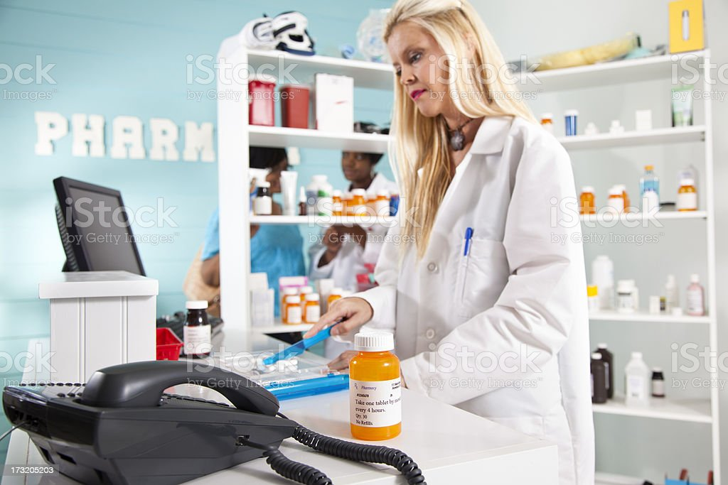 Pharmacist counting pills focus on bottle in foreground royalty-free stock photo